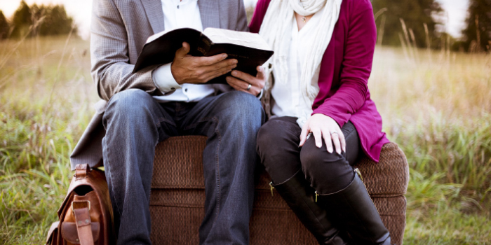Pastor and wife sitting on couch together reading the Bible