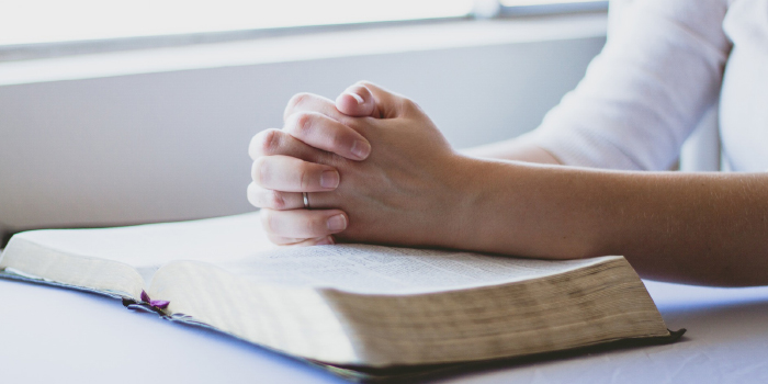 Woman sitting with hands folded praying next to her Bible