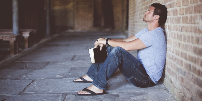 Man sitting with his back against a brick wall looking tired