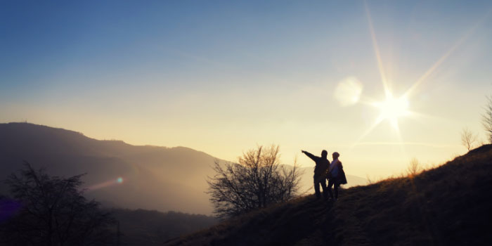 Silhouette of man and woman outdoors looking out over a ridge