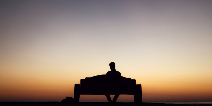 Silhouette of a man waiting on a park bench in the sunset