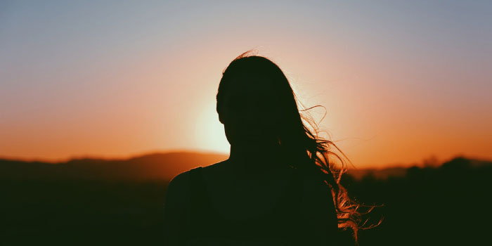 Silhouette of woman looking out on a sunset sky