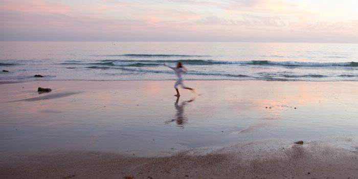 Woman running down a sunset beach