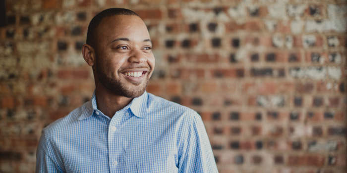 Smiling African-American man against brick background