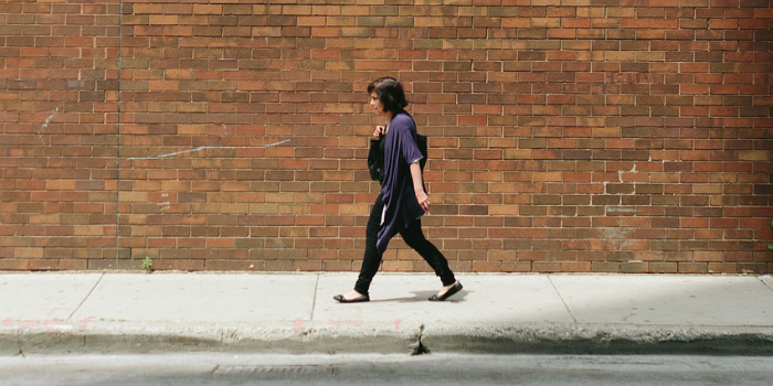 Woman walking down sidewalk against brick wall