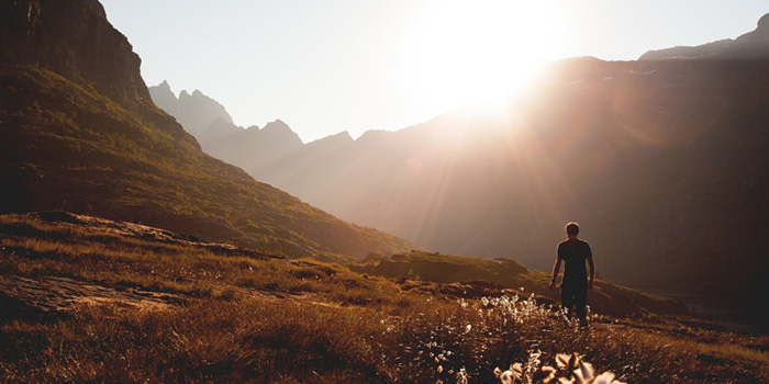 Man standing in a valley in the sunlight