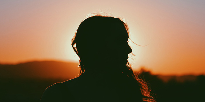 Silhouette of woman staring off to the side
