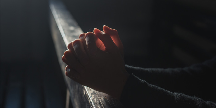 Close up on the hands of a woman praying in a darkened room