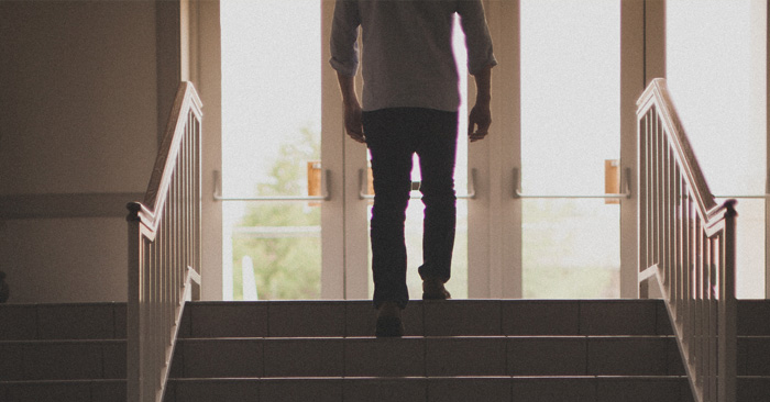 Man walking up steps out of church