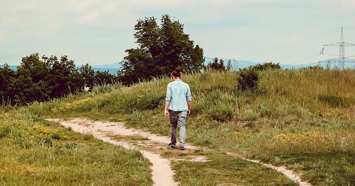 Woman walking down a dirt road alone