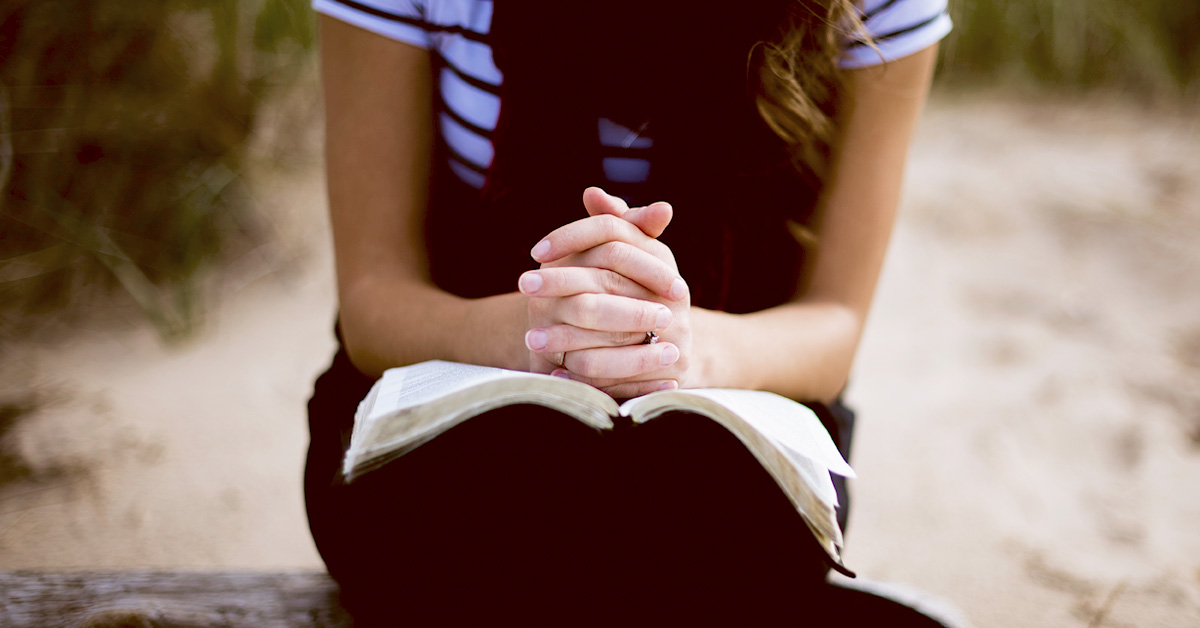 Woman sitting down praying with a bible in her lap