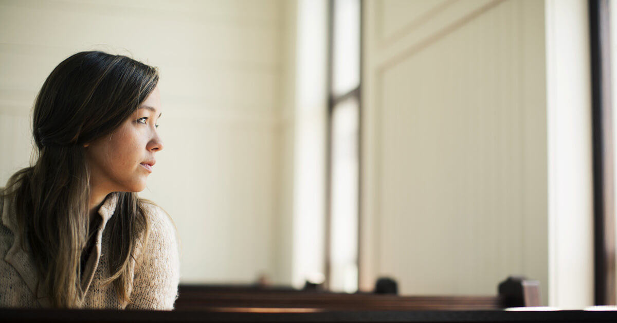 Woman sitting in a church pew looking out a window