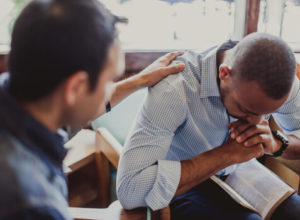 Two men praying and receiving counseling