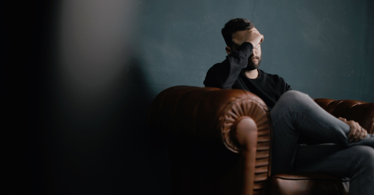 Man sitting in a chair looking depressed