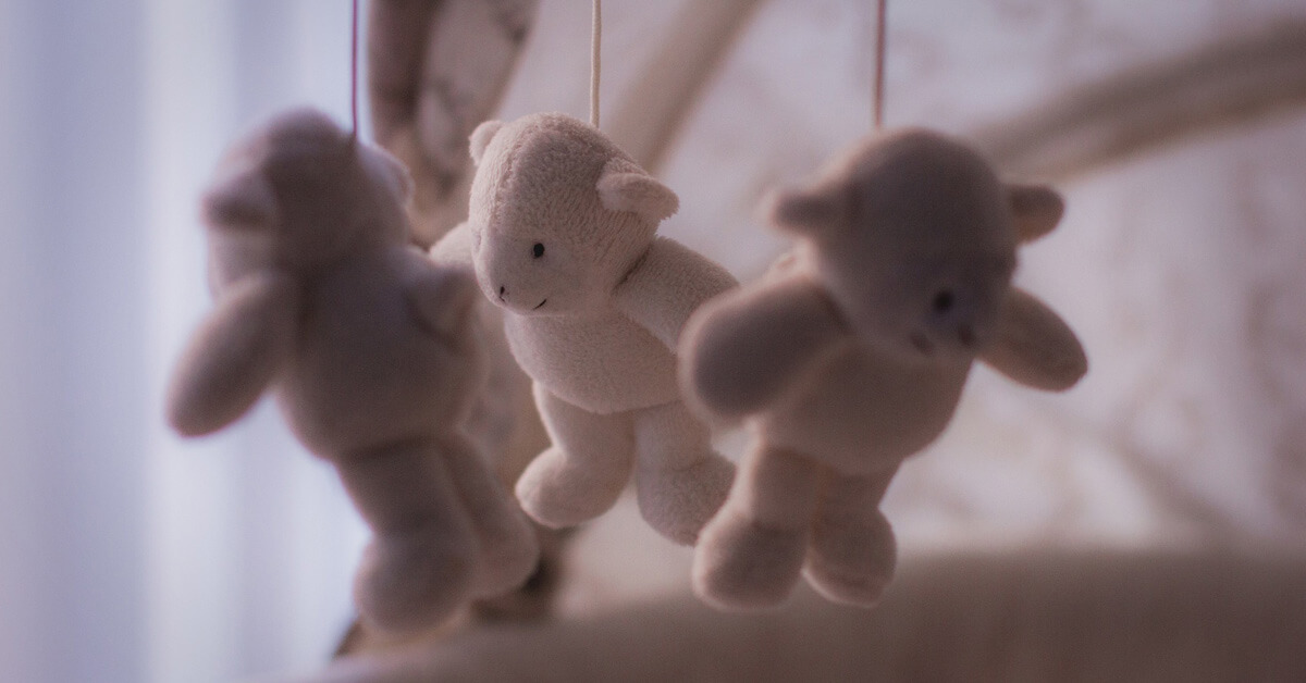 Stuffed bears hanging over cradle