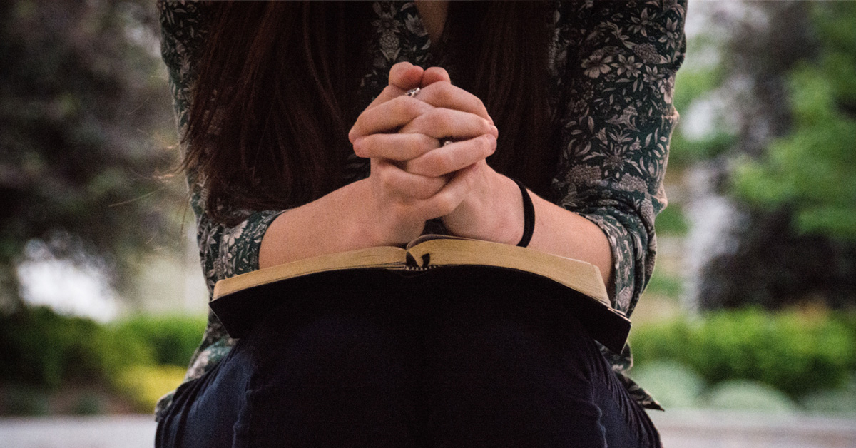 Woman sitting and praying with her Bible
