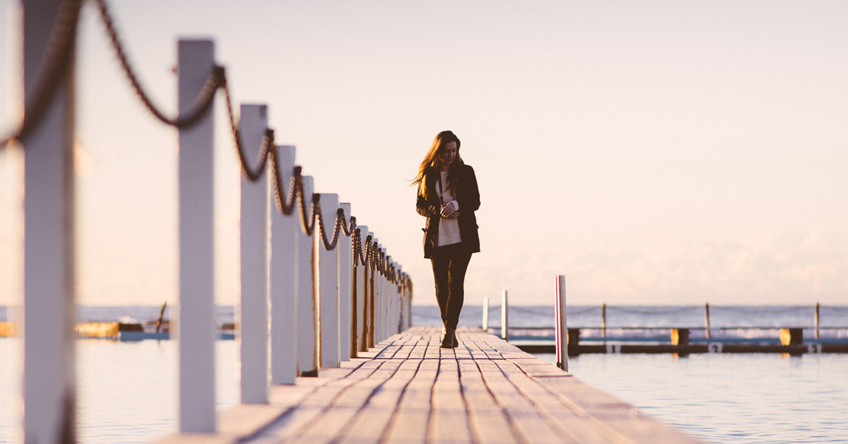 Woman walking across a pier