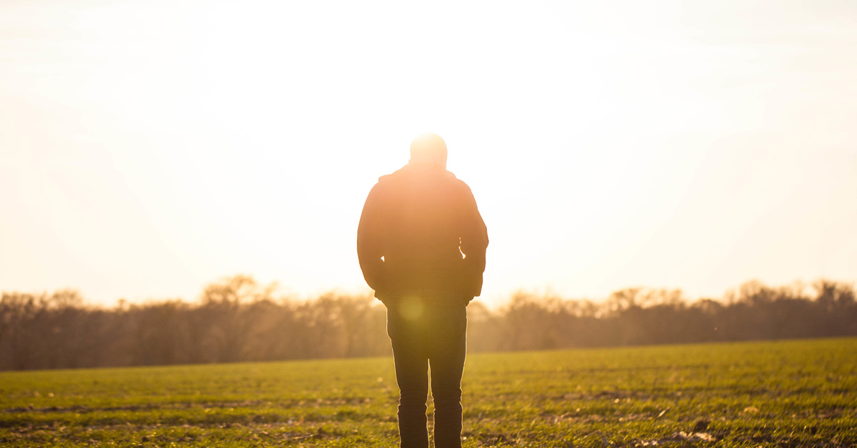 Man in a field at sunrise looking down