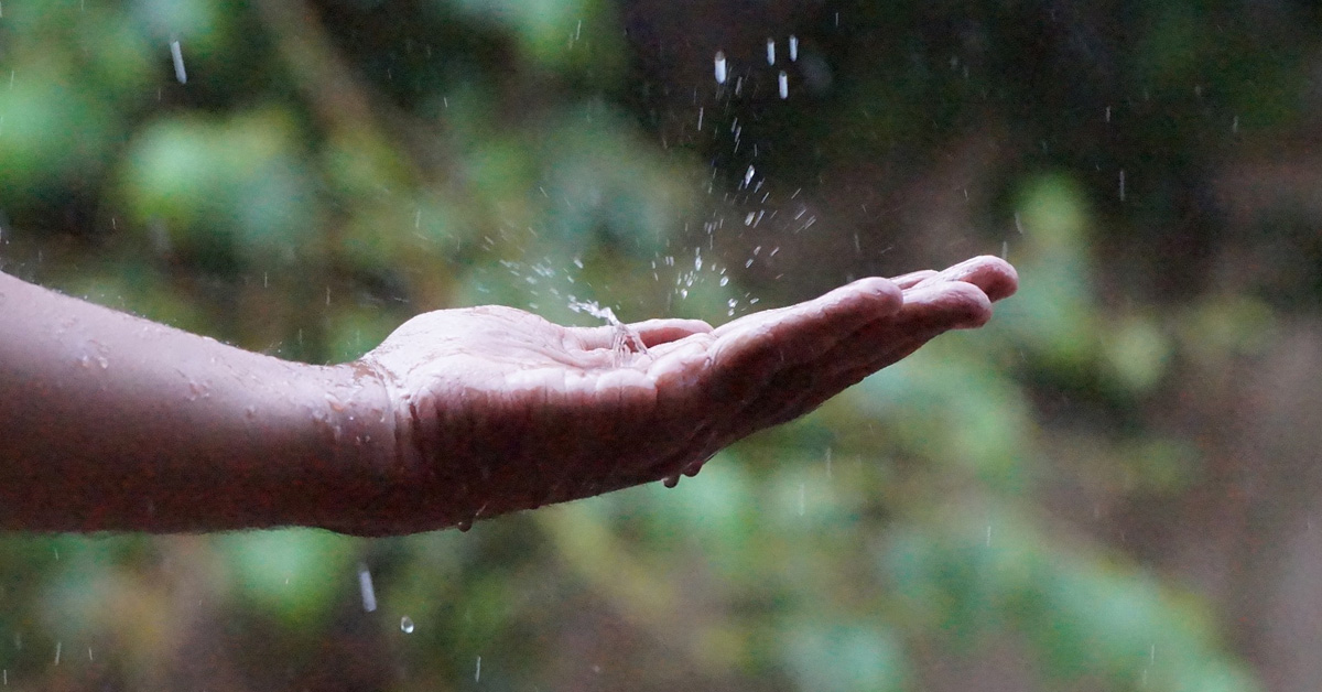 Hand reaching out to catch the rain