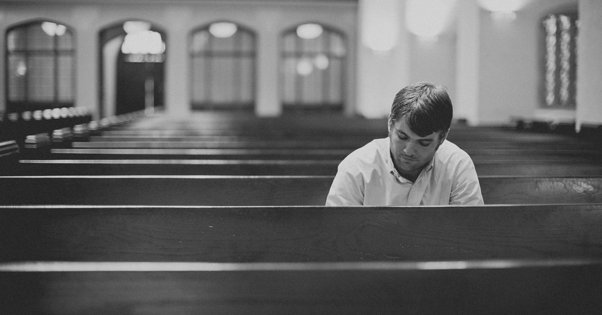 A man sitting in a pew alone in a church sanctuary