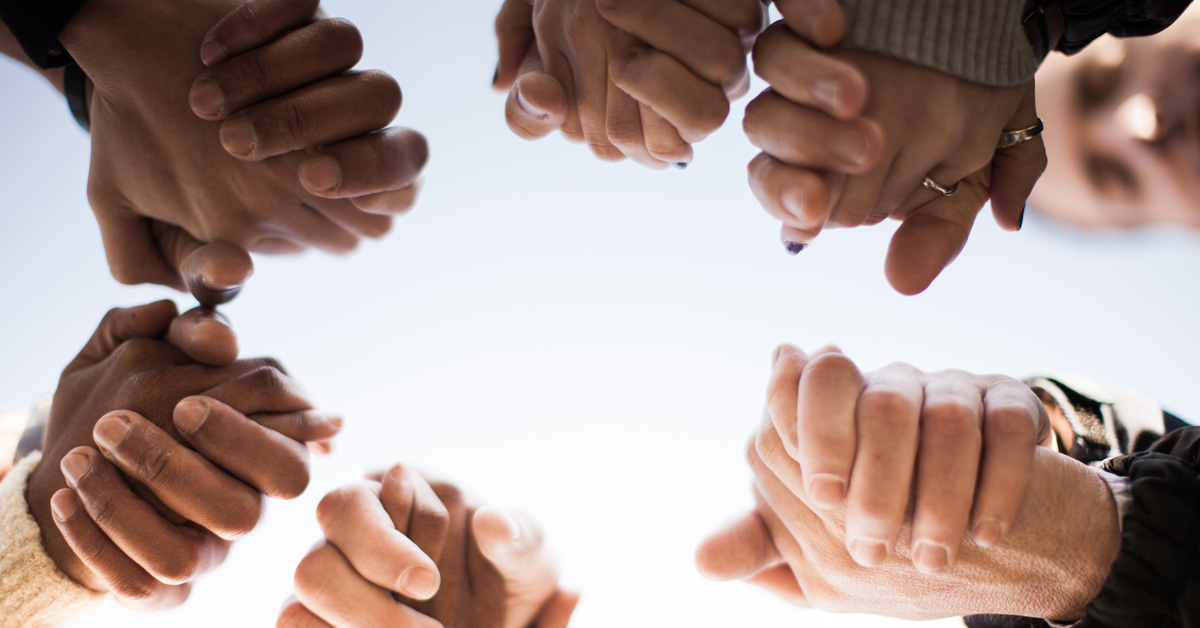 People holding hands in prayer