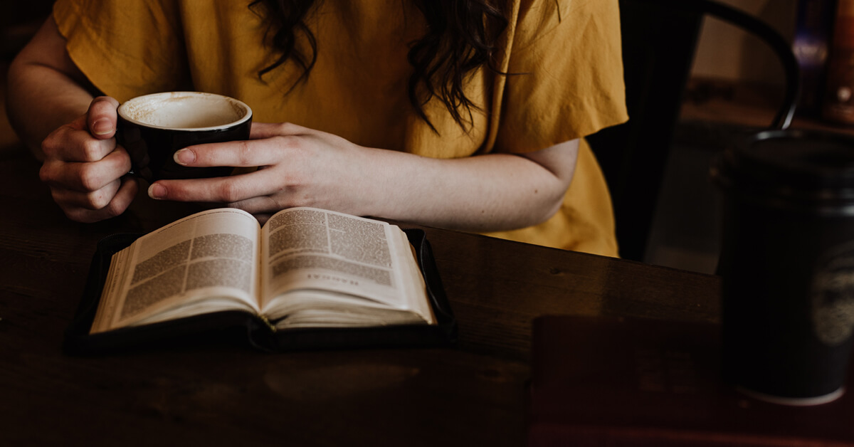 Woman reading bible with cup of coffee in hand